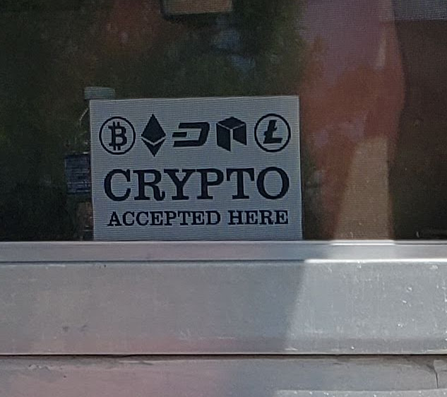 "Sign reading ""Crypto accepted here, with the icons of various cryptocurrencies"" in the window of a food truck."